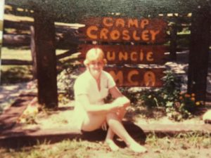 old school Renee in front of Camp Crosley sign